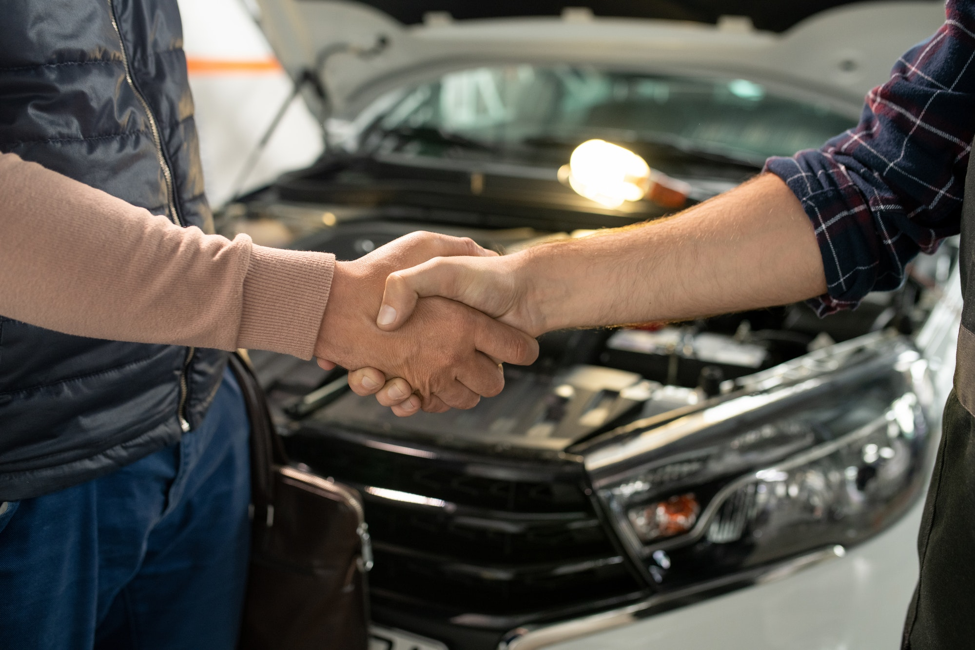 Young contemporary technician of car service shaking hand of male client